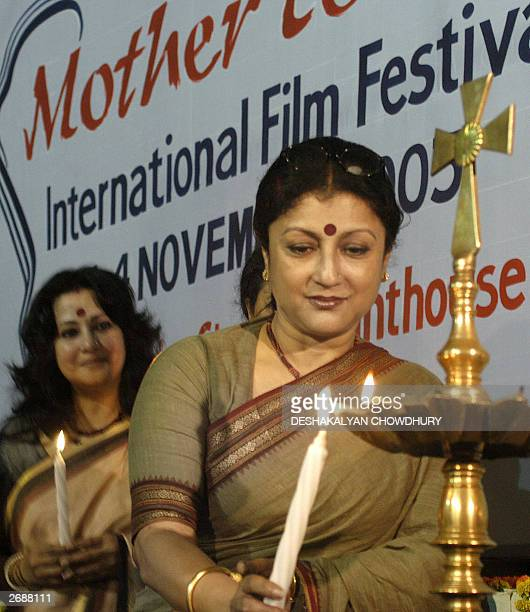 Indian film actress turned director Aparna Sen lights a candle while actress Munmun Sen looks on during the opening ceremony of the 'Mother Teresa...