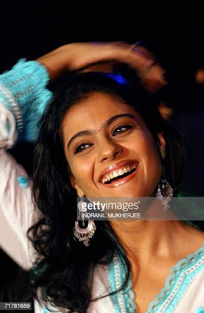 Indian film Indian actress Kajol adjusts her hair as she speaks at a function to launch replica dolls of Bollywood stars in Mumbai 04 September 2006...