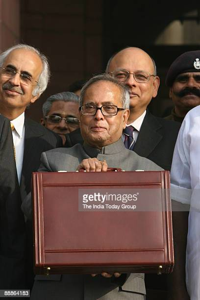 Indian finance Minister Pranab Mukherjee poses with his briefcase as he arrives at Parliament to present the interim budget in New Delhi on February...