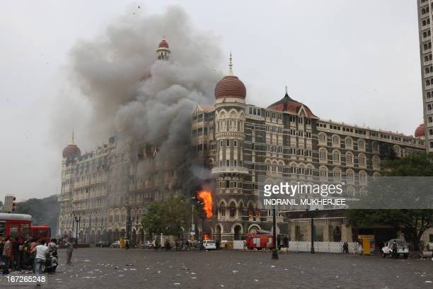 Indian fire brigade officials and bystanders look towards The Taj Mahal hotel in Mumbai on November 29 as smoke and flames billow out from a section...