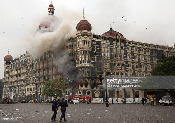Indian Fire brigade officials walk towards The Taj Mahal hotel in Mumbai on November 29 as smoke and flames billow out from a section of the building...