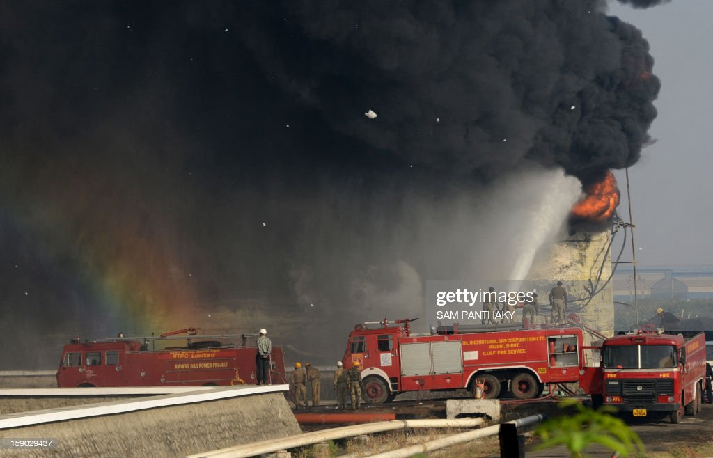 Indian fire fighters battle to douse the flames of a burning fuel tank containing almost 5,000 kilolitres of petrol at the Indian Oil Corporation (IOC) plant at Hajira near Surat, some 275 kms from Ahmedabad on January 6, 2013. Three persons were killed in a major fire in a storage tank of IOC terminal, which was contained after a 21-hour operation by fire brigade team, officials said according to the Press Trust of India (PTI). AFP PHOTO / Sam PANTHAKY