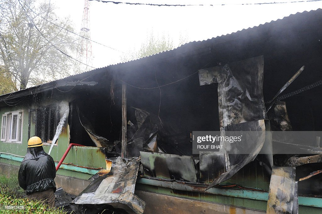 Indian fire fighters try to extinguish a fire at tourism department office in Srinagar on April 7, 2013. A fire broke out in a building, housing the office of the Director Tourism (Kashmir) there was no loss of life or injury to anyone, police said. AFP PHOTO/ Rouf BHAT