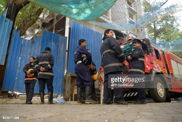 Indian fire officials are seen at the scene of a fire at a building construction site in Mumbai on September 7 2017 Six people were killed and twelve...
