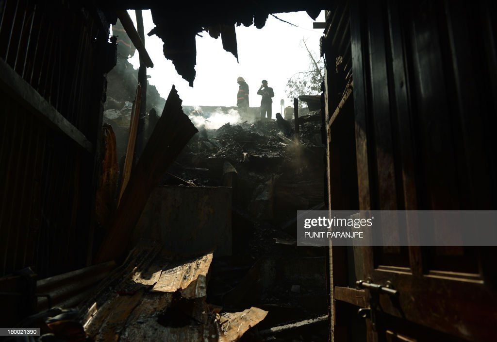Indian fire officials are seen through damaged houses after a fire raged through the Nayanagar slum in Mumbai on January 25, 2013. A fire killed six people when it ripped through a slum in the heart of Mumbai on January 25 and left hundreds homeless, emergency services said.