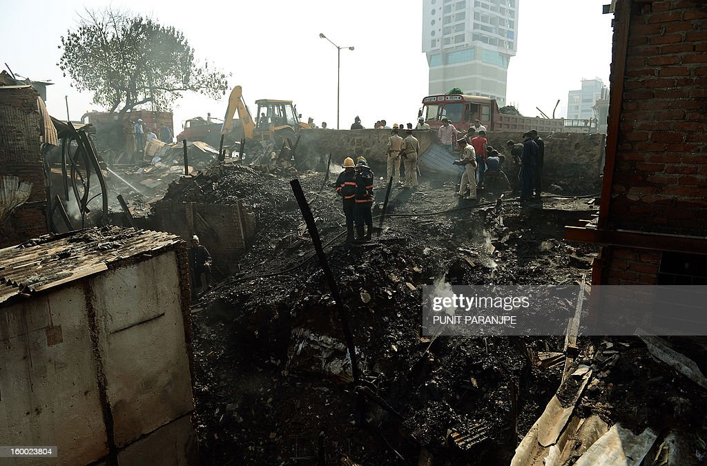 Indian fire officials stand amidst the debris of burnt houses after a fire raged through the Nayanagar slum in Mumbai on January 25, 2013. A fire killed six people when it ripped through a slum in the heart of Mumbai on January 25 and left hundreds homeless, emergency services said.