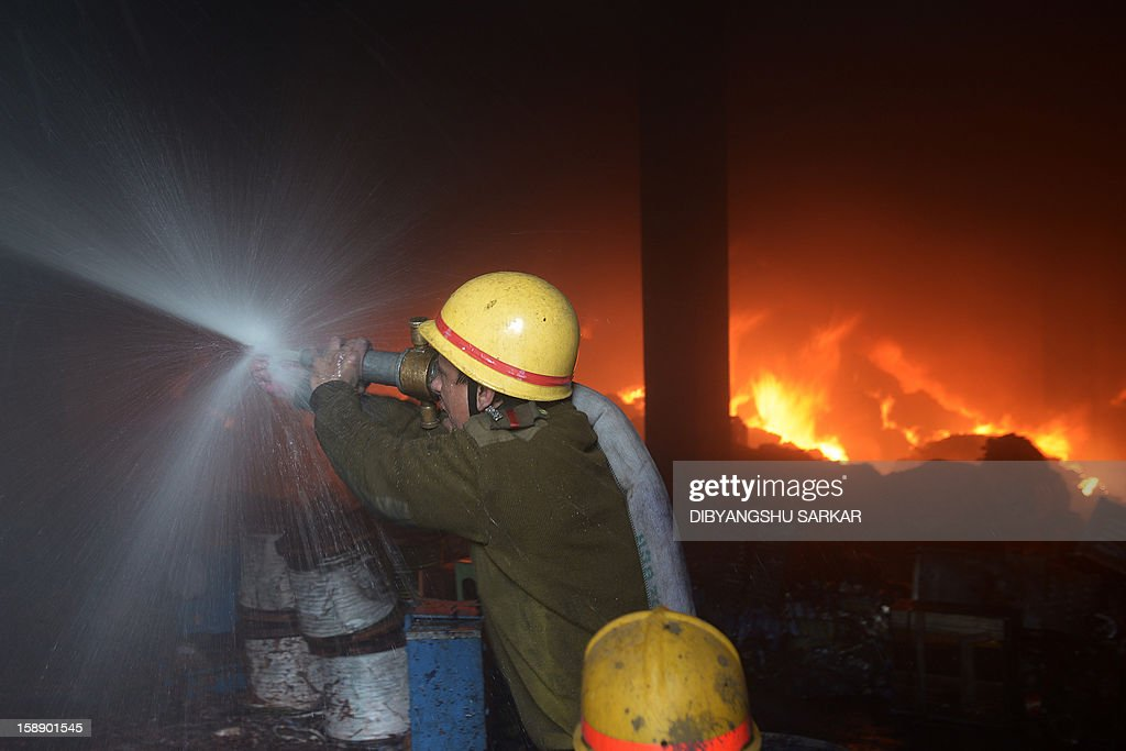 Indian firefighters attempt to control a blaze at a godown in Kolkata on January 3, 2013. A fire destroyed a century old warehouse at Burrabazar, the commercial hub of the eastern region, destroying goods comprising cloth and other inflammable material, a report said. AFP PHOTO/Dibyangshu SARKAR