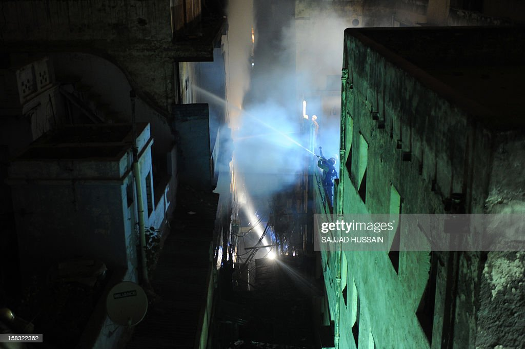 Indian firefighters attempt to control a fire that broke out at an electronics market in the old quarters of New Delhi on December 13, 2012. The fire was reported to be triggered by a short circuit in one of the shops in the congested market packed with outlets selling electrical equipment. AFP PHOTO/ SAJJAD HUSSAIN