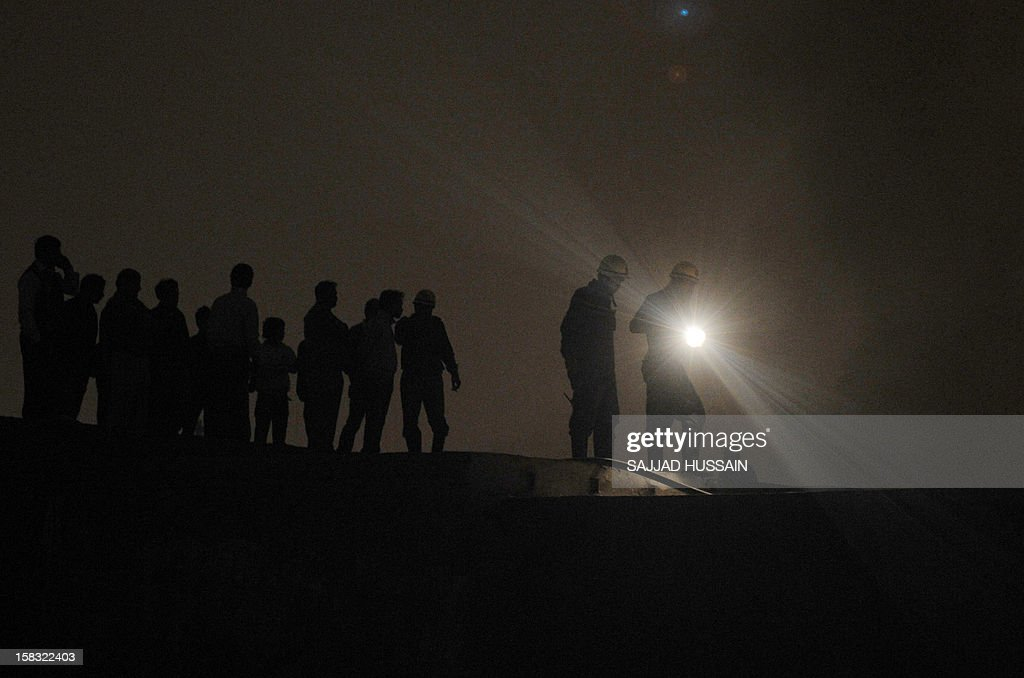 Indian firefighters attempt to control a fire that broke out at an electronics market as residents look on in the old quarters of New Delhi on December 13, 2012. The fire was reported to be triggered by a short circuit in one of the shops in the congested market packed with outlets selling electrical equipment.