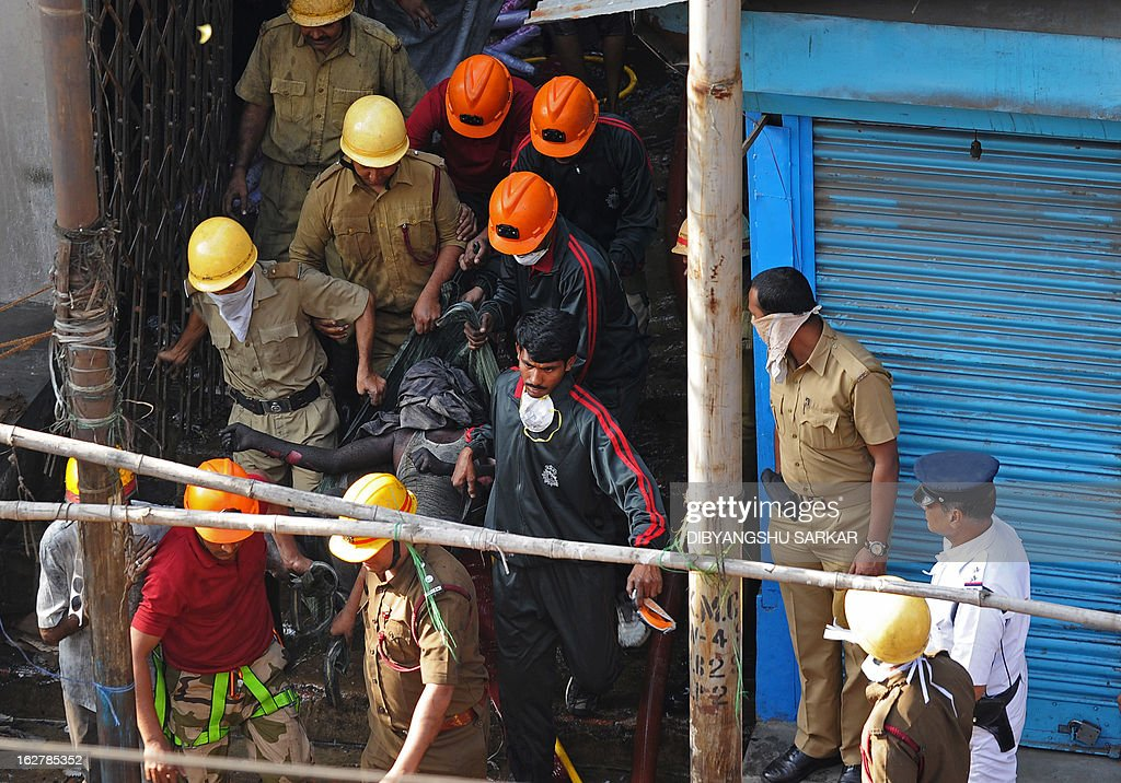 Indian firefighters carry out the body of a blaze victim from the Surya Sen market building in Kolkata on February 27, 2013. A fire swept through a six-storey building housing an illegal market in the eastern Indian city of Kolkata, killing 13 people who were unable to escape the inferno, local officials said. AFP PHOTO/Dibyangshu SARKAR