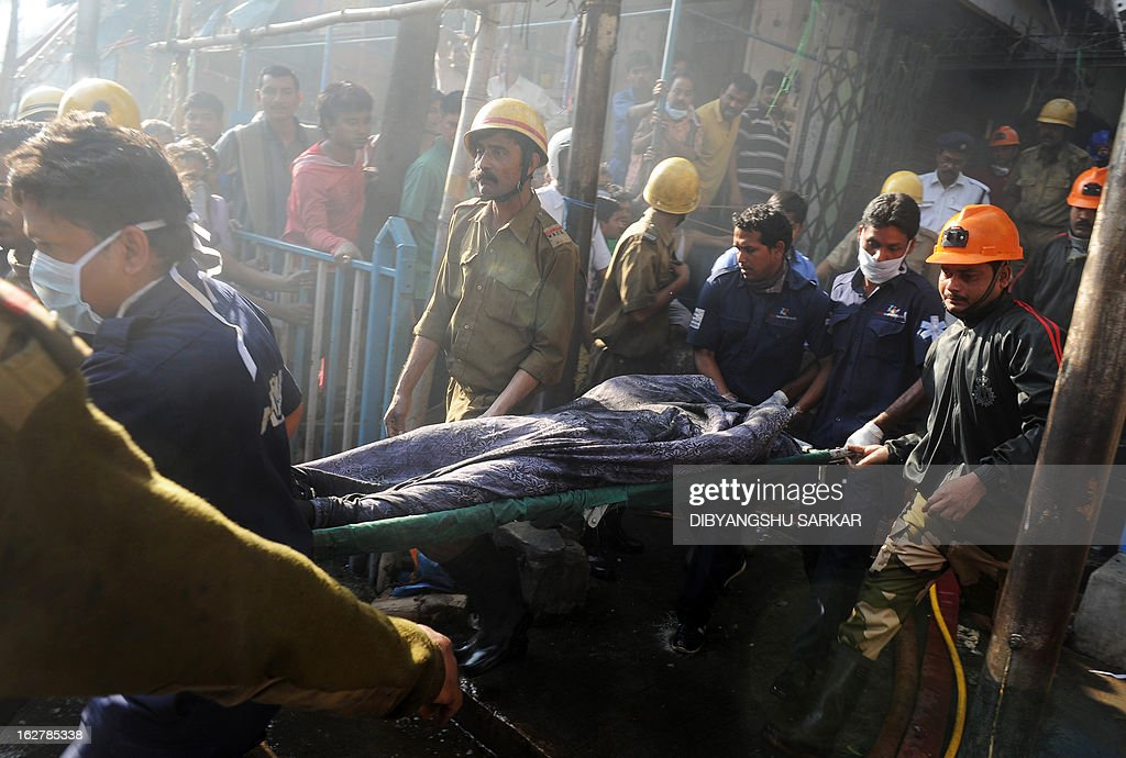 Indian firefighters carry out the remains of a blaze victim from the Surya Sen market building in Kolkata on February 27, 2013. A fire swept through a six-storey building housing an illegal market in the eastern Indian city of Kolkata, killing 13 people who were unable to escape the inferno, local officials said. AFP PHOTO/Dibyangshu SARKAR
