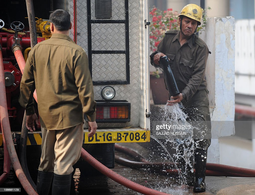Indian firefighters clean up after fighting a blaze that broke out in a fifteen story building in New Delhi early November 19, 2012. No casualities were reported in the fire.