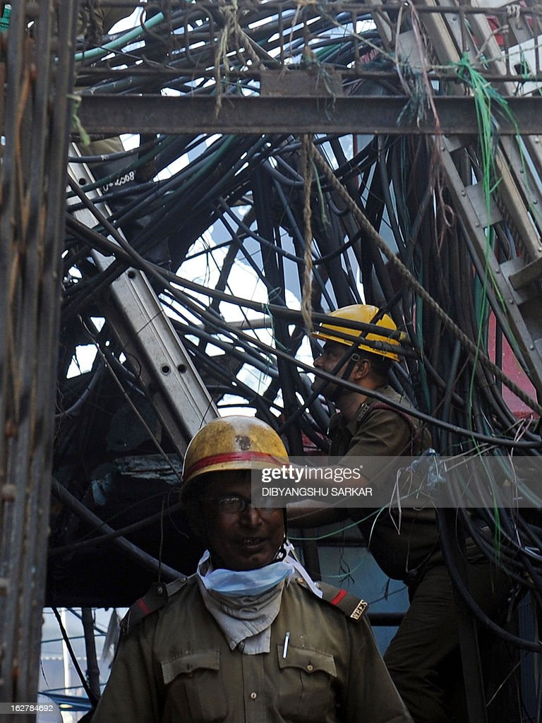 Indian firefighters climb past wiring as they attempt to control a blaze in the Surya Sen market building in Kolkata on February 27, 2013. A fire swept through a six-storey building housing an illegal market in the eastern Indian city of Kolkata, killing 13 people who were unable to escape the inferno, local officials said. AFP PHOTO/Dibyangshu SARKAR