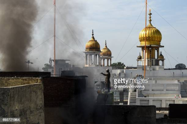 Indian firefighters contain a fire which broke out in Kinari Bazaar in the Chandni Chowk area of New Delhi on June 8 2017 No casualties were reported...