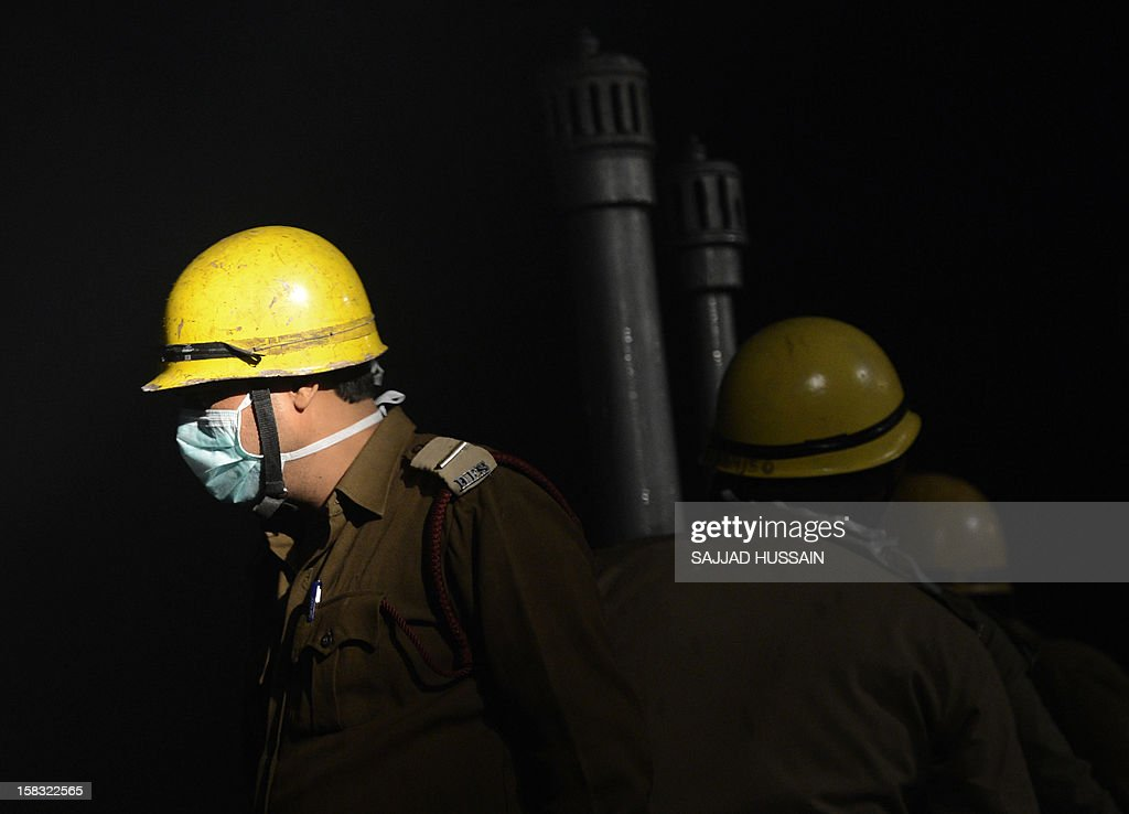 Indian firefighters look on as they attempt to control a fire that broke out at an electronics market in the old quarters of New Delhi on December 13, 2012. The fire was reported to be triggered by a short circuit in one of the shops in the congested market packed with outlets selling electrical equipment. AFP PHOTO/ SAJJAD HUSSAIN