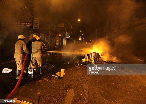 Indian firefighters use a hose as they attempt to extinguish burning material on a street in Jammu late August 10 during a curfew in the winter...