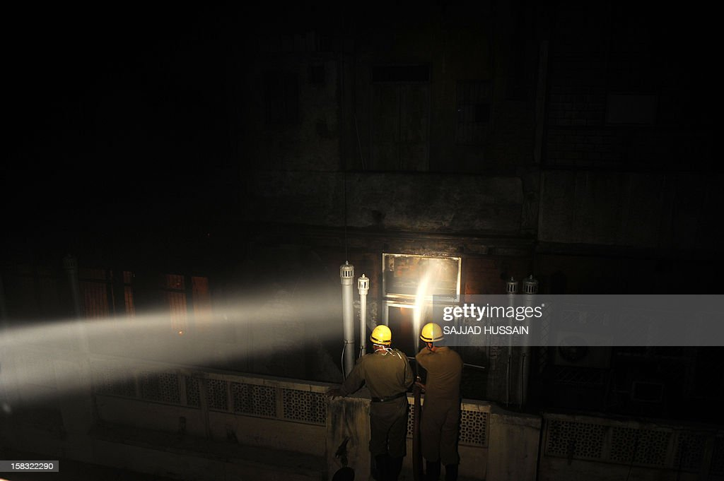 Indian firefighters uses a hose in an attempt to control a fire that broke out at an electronics market in the old quarters of New Delhi on December 13, 2012. The fire was reported to be triggered by a short circuit in one of the shops in the congested market packed with outlets selling electrical equipment. AFP PHOTO/ SAJJAD HUSSAIN