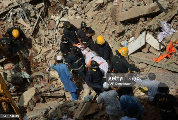 Indian firemen carry the body of a victim out of the debris of a collapsed building in Mumbai on August 31 2017 At least 12 people died August 31...