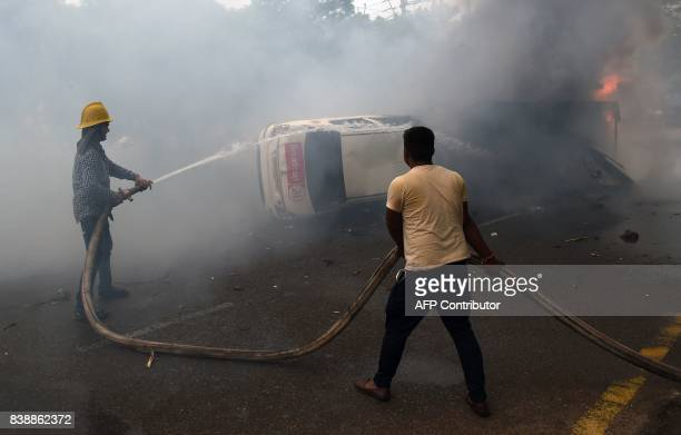 Indian firemen douse a burned media vehicle during clashes between the controversial guru's followers and security forces in Panchkula on August 25...