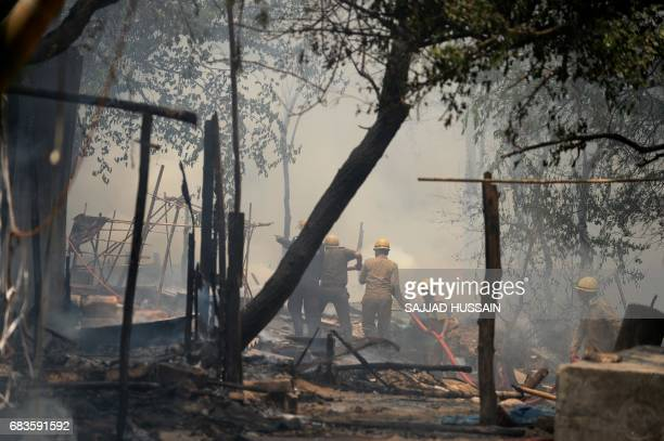 Indian firemen douse a fire that broke out in a makeshift settlement in New Delhi on May 16 2017 / AFP PHOTO / SAJJAD HUSSAIN