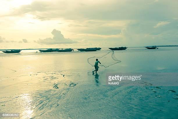 Indian fisherman catch fish during sunset