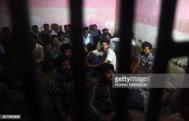 TOPSHOT Indian fisherman sit in a police lockup in Karachi on March 26 2017 after they were arrested by Pakistan coast guards Pakistan has arrested...