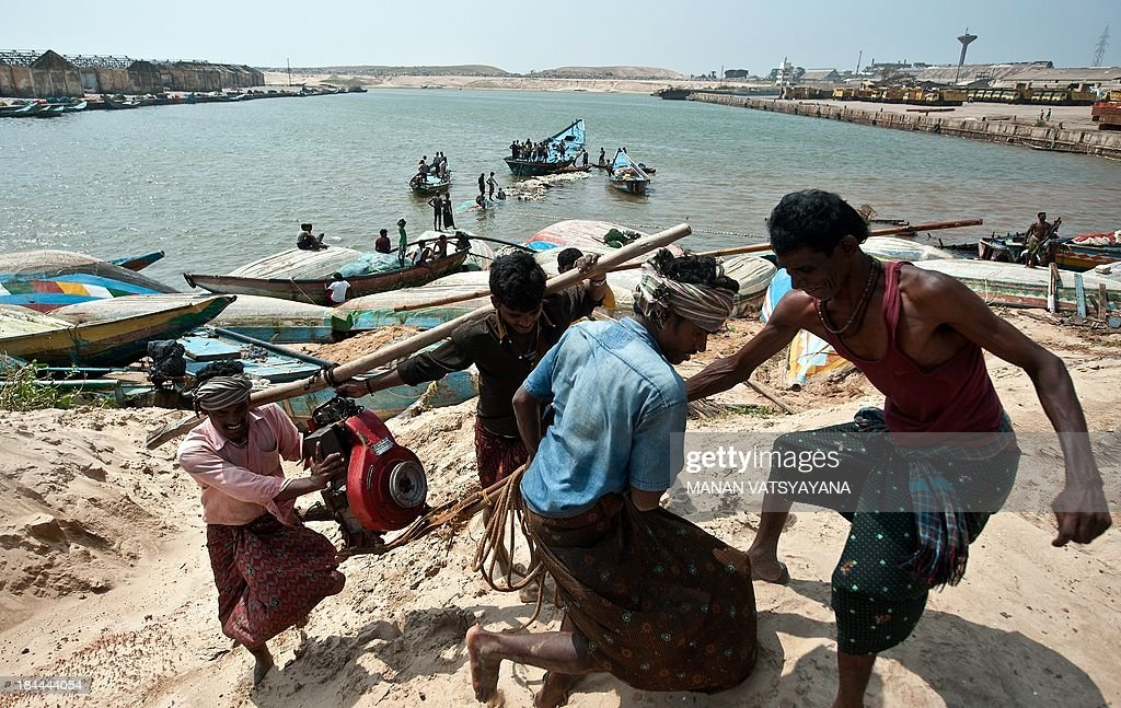 Indian fishermen carry a motor they salvaged from a damaged boat at the Gopalpur Port on October 14, 2013. - Hundreds of thousands of people who fled India's strongest cyclone in 14 years returned home to scenes of devastation, as survivors stranded at sea during the storms were finally rescued. AFP PHOTO/ MANAN VATSYAYANA