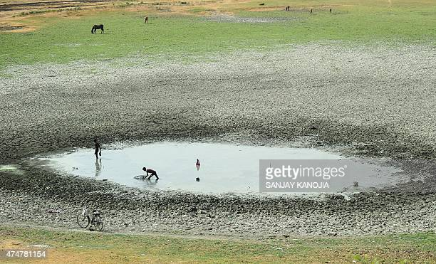 Indian fishermen catch fish in a shrunken pond in the village of Phaphamau on the outskirts of Allahabad on May 26 2015 At least 800 people have died...