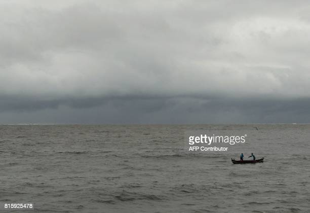 Indian fishermen collect their net as dark clouds gather over the Arabian Sea in Mumbai on July 17 2017 PARANJPE