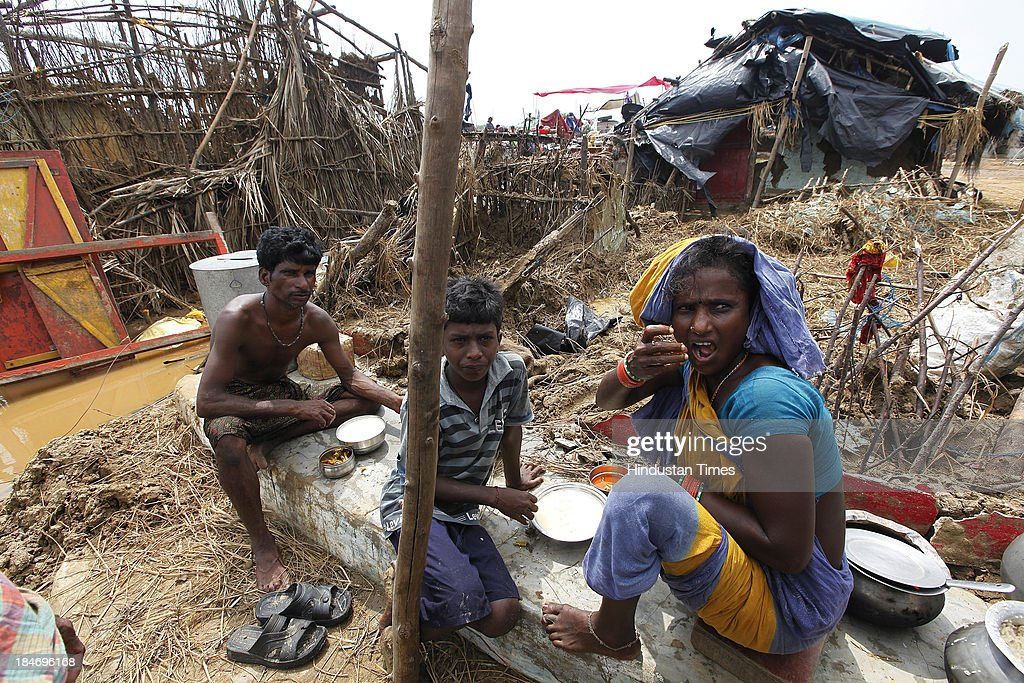 Indian fishermen family eating rice and fish near their damaged houses after cyclone Phailin in Podampetta village on October 15, 2013 about 190 kilometers south from Bhubaneswar, India. Cyclone Phailin on Sunday left a trail of destruction knocking down lakhs of homes affecting nearly 90 lakh people and destroying paddy crops worth about Rs 2,400 crore, but Odisha and Andhra Pradesh escaped from widespread loss of life due to timely and efficient evacuation efforts .