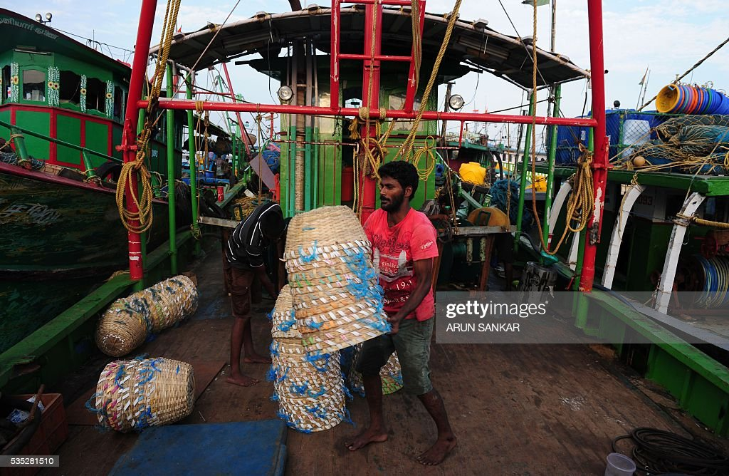 Indian fishermen load baskets onto mechanised boats in Chennai on May 29, 2016, as they prepare to set sail after a 45 day fishing ban on the east coast of India. Authorities in the southern Indian state of Tamil Nadu, had imposed a 45 day ban on fishing by mechanised vessels to protect marine life with only 'country boats' operating within five nautical miles of the coast exempted in the seas of The Bay of Bengal. / AFP / ARUN