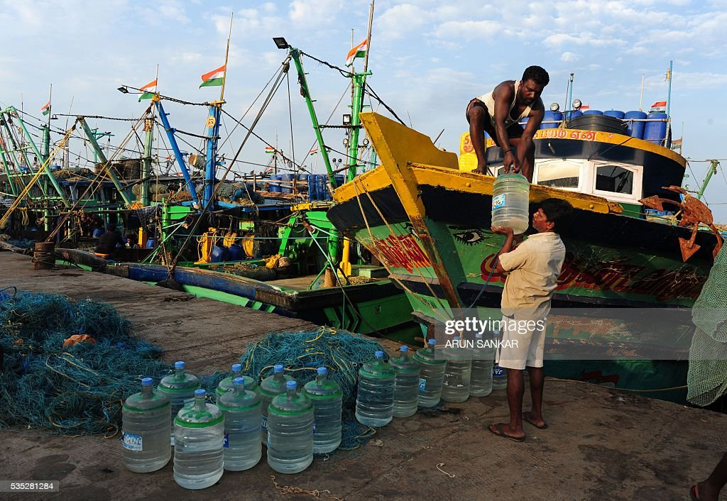 Indian fishermen load bottles of drinking water onto mechanised boats in Chennai on May 29, 2016, as they prepare to set sail after a 45 day fishing ban on the east coast of India. Authorities in the southern Indian state of Tamil Nadu, had imposed a 45 day ban on fishing by mechanised vessels to protect marine life with only 'country boats' operating within five nautical miles of the coast exempted in the seas of The Bay of Bengal. / AFP / ARUN