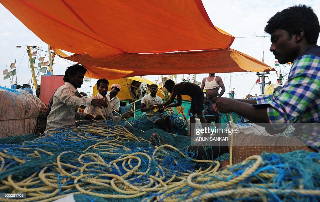 Indian fishermen load their nets onto mechanised boats in Chennai on May 29, 2016, as they prepare to set sail after a 45 day fishing ban on the east coast of India. Authorities in the southern Indian state of Tamil Nadu, had imposed a 45 day ban on fishing by mechanised vessels to protect marine life with only 'country boats' operating within five nautical miles of the coast exempted in the seas of The Bay of Bengal. / AFP / ARUN