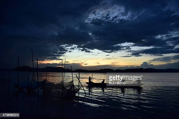 Indian fishermen paddle a boat on the Brahmaputra River in Guwahati the capital of the northeastern state of Assam on July 8 2015 AFP PHOTO / Biju...