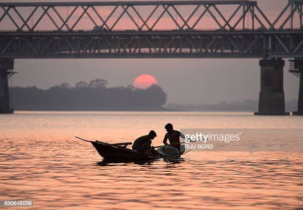 Indian fishermen paddle their boats back after fishing in the Brahmaputra River on the outskirts of Guwahati the capital of the northeastern state of...