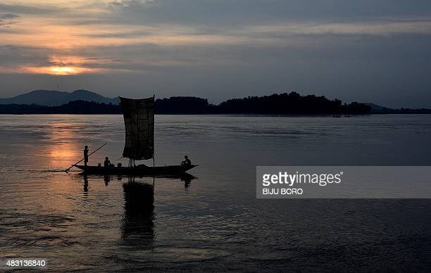Indian fishermen paddle their down the Brahmaputra River during sunset in Guwahati on August 6 2015 The Brahmaputra originates in Tibet where it is...