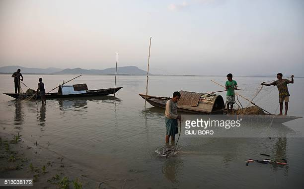 Indian fishermen prepare their fishing net on the Brahmaputra River in Guwahati on February 29 2016 India pledged to spend USD 52 billion dollars to...