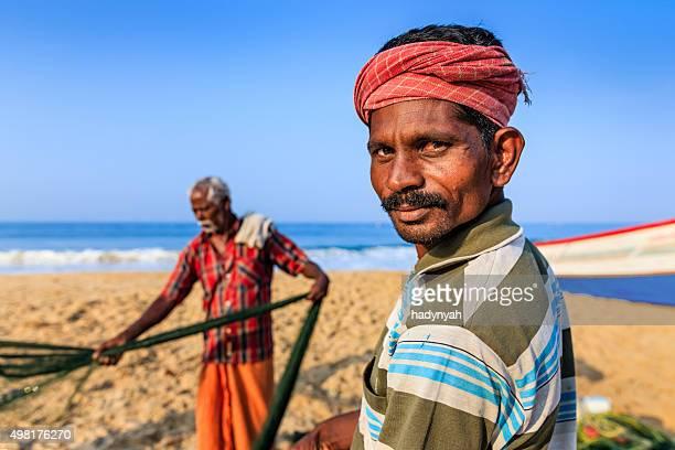 Indian fishermen preparing fishing nets, Kerala, India