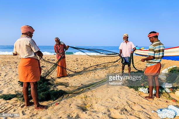 Indian fishermen preparing fishing nets, Kerala, India