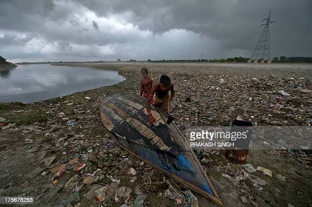Indian fishermen repair their boat on the banks of the Yamuna river in Noida some 30 kms east of New Delhi on August 6 2013 The monsoon which covers...