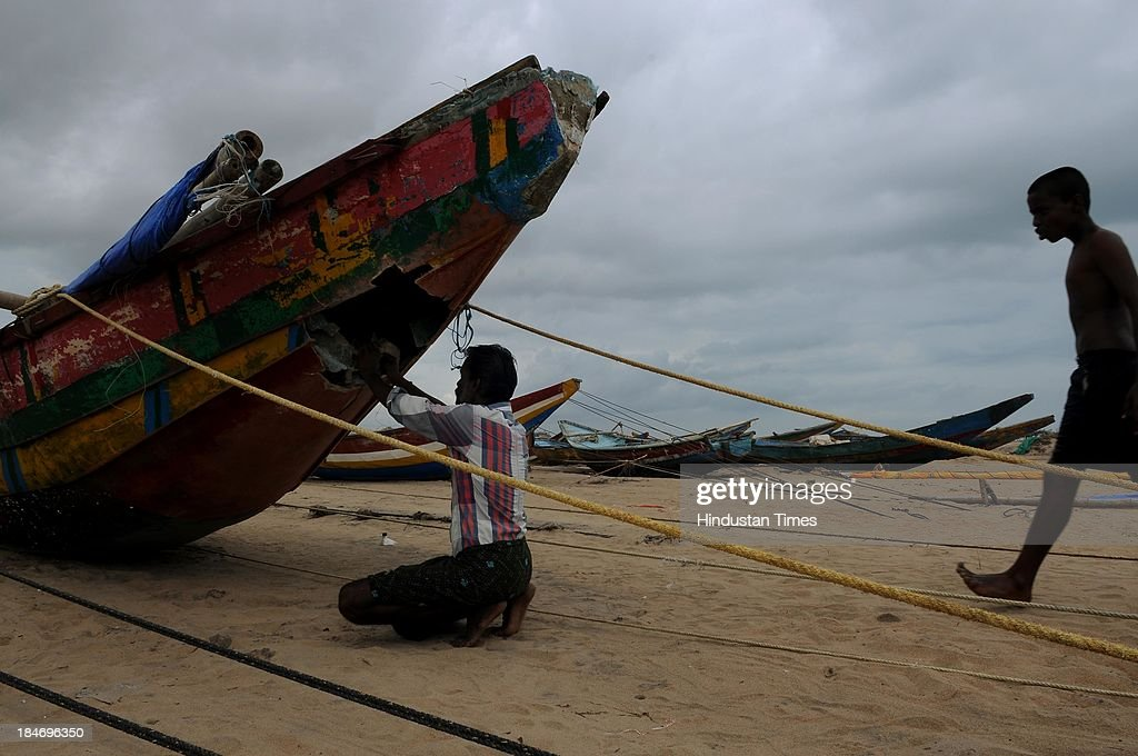Indian fishermen repairing his boat on seacoasts at Gopalpur after the cyclone Phailin on October 15, 2013 in Chattapur, India. Cyclone Phailin on Sunday left a trail of destruction knocking down lakhs of homes affecting nearly 90 lakh people and destroying paddy crops worth about Rs 2,400 crore, but Odisha and Andhra Pradesh escaped from widespread loss of life due to timely and efficient evacuation efforts .
