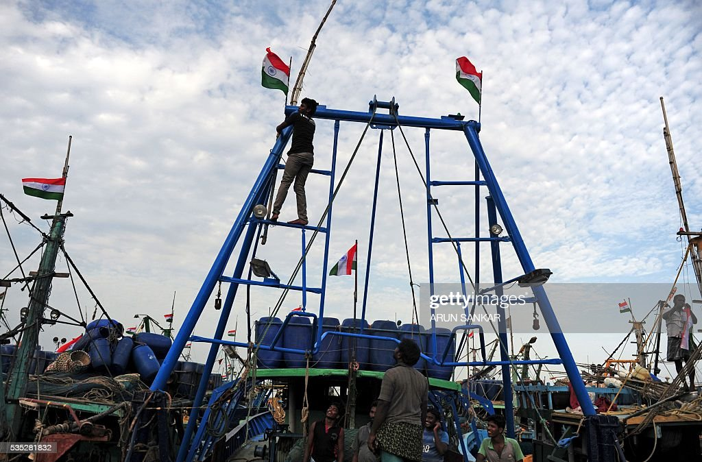 Indian fishermen tie a national flag onto their mechanised boat in Chennai on May 29, 2016, as they prepare to set sail after a 45 day fishing ban on the east coast of India. Authorities in the southern Indian state of Tamil Nadu, had imposed a 45 day ban on fishing by mechanised vessels to protect marine life with only 'country boats' operating within five nautical miles of the coast exempted in the seas of The Bay of Bengal. / AFP / ARUN