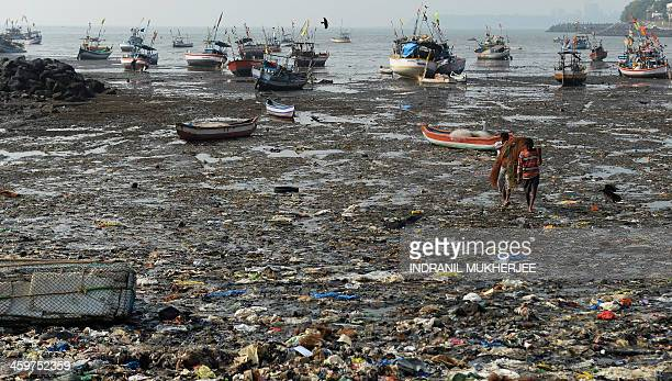Indian fishermen walk through a beach littered with garbage as they carry their nets back from their boat near a fishing village in Mumbai on...
