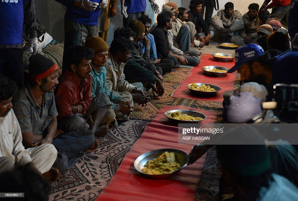 Indian fishermen, who were arrested for illegally fishing into Pakistan's territorial waters, sit to have dinner at a police station in Pakistan's port city of Karachi on February 2, 2013. Pakistan maritime security agency has arrested 54 Indian fishermen and seized nine boats for illegally fishing in Pakistan's territorial waters. AFP PHOTO/Asif HASSAN