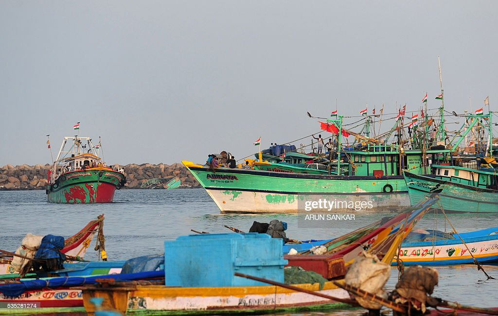 Indian fishermen works on mechanised boats in Chennai on May 29, 2016,as they prepare to set sail after a 45 day fishing ban on the east coast of India. Authorities in the southern Indian state of Tamil Nadu, had imposed a 45 day ban on fishing by mechanised vessels to protect marine life with only 'country boats' operating within five nautical miles of the coast exempted in the seas of The Bay of Bengal. / AFP / ARUN