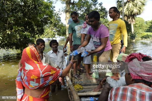 Indian flood effected villagers collect drinking water and relief food at Alal village in Malda district in the Indian state of West Bengal on August...