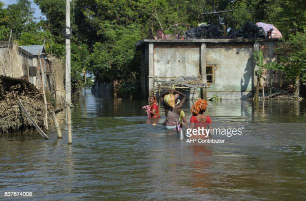 Indian flood effected villagers wade through flood waters at Alal village in Malda in the Indian state of West Bengal on August 23 2017 More than 750...