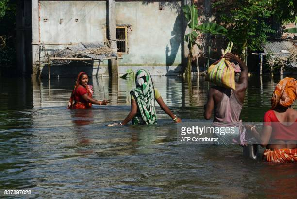 Indian flood effected villagers wade through flood waters at Alal village in Malda district in the Indian state of West Bengal on August 23 2017 More...