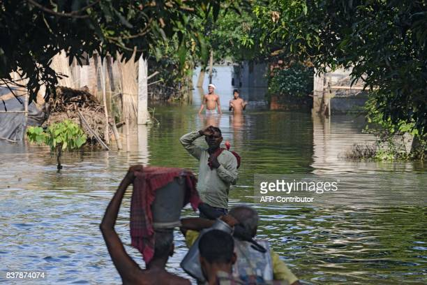 Indian flood effected villagers wade through flood waters in Alal village in Malda in the Indian state of West Bengal on August 23 2017 More than 750...