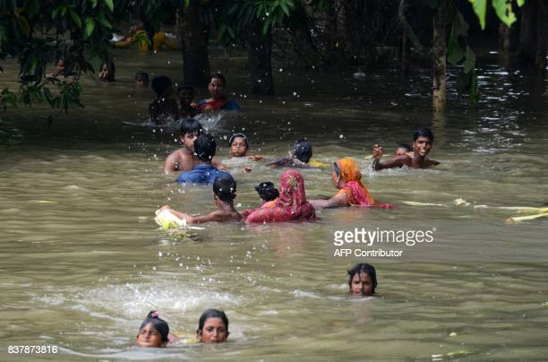 Indian flood effected villagers wades and swim through flood waters in Alal village in Malda in the Indian state of West Bengal on August 23 2017...